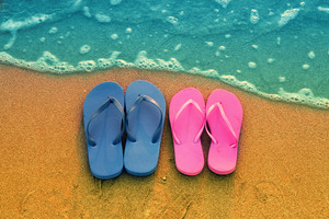 Romantic beach scene. Female and male flip flpp sandals on the beach