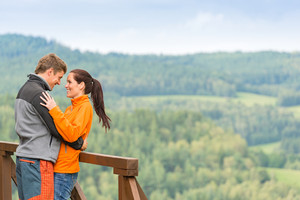 Romantic couple looking at each other on landscape background