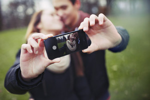 Romantic teenage couple taking self portrait with cell phone at the park. Young man and woman in love. Asian male and female model.