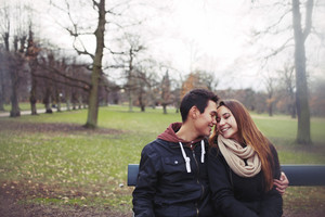 Romantic young couple sitting on a park bench outdoors in winter. Mixed race teenage couple together with copyspace.
