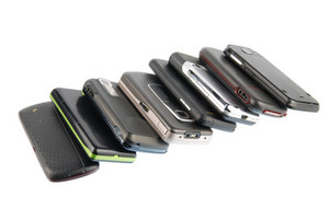 Row Of Modern Mobile Phones On White