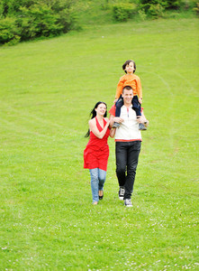 running family on green meadow in nature