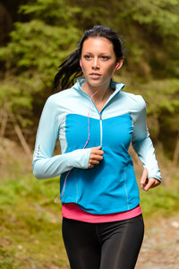 Running woman with headphones outdoor close-up