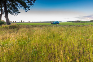 Rural grassland landscape with green off-road car. Beautiful rural countryside at summer.