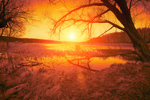 Rural landscape. Orange sunset over lake