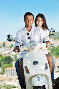 Portrait Of Happy Young Love Couple On Scooter Enjoying Summer Time