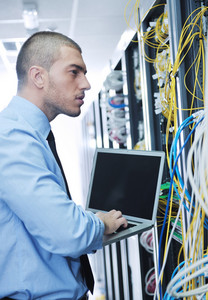 Businessman with laptop in network server room