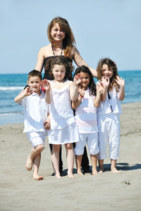 Group Portrait Of Childrens With Teacher On Beach