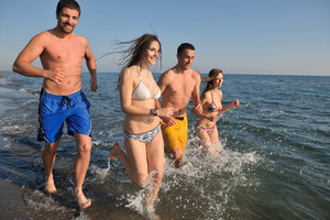 Happy People grupo têm o divertimento eo corredor na praia