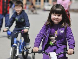 Happy childrens group learning to ride bicycle