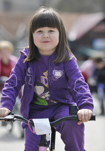 Cute little girl riding bicycle on sunny day