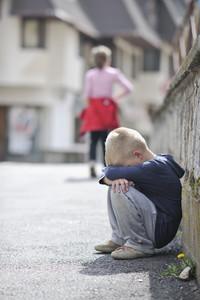 Sad lonely boy on street