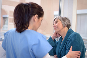 Sad senior patient in hospital corridor looking outside with young nurse