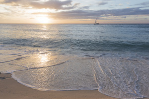 Sailboat and gentle waves on the beach at sunrise