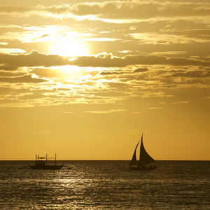 Sailboat being towed on the ocean at sunset