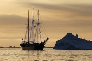 Sailboat traveling by an iceberg during a rosy sunset