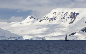 Sailboat traveling past a sunlit, snowy coast