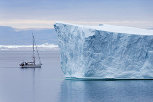 Sailboat traveling past a towering iceberg