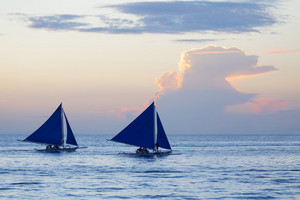 Sailboats in the ocean at sunset