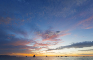 Sailboats in the ocean during a dramatic sunset