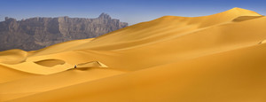 Sand dunes and distant rocky cliffs in the desert