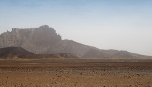 Sandy desert and distant rocky cliffs
