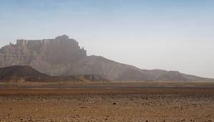 Sandy desert and distant rocky cliffs