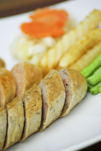 Sausage and potato fries on white dish
