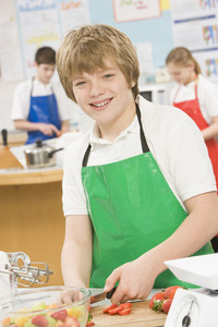 Schoolboy at school in a cooking class