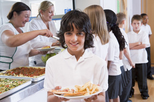 Schoolboy holding plate of lunch in school cafeteria