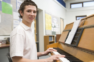 Schoolboy playing piano in music class