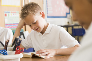 Schoolboy reading a book in class