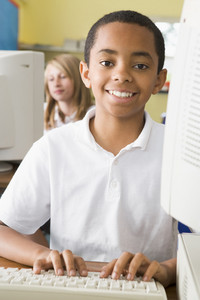 Schoolboy studying in front of a school computer