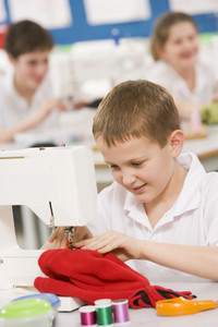 Schoolboy using a sewing machine in sewing class