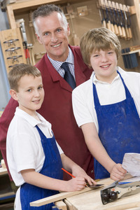 Schoolboys and teacher in woodwork class