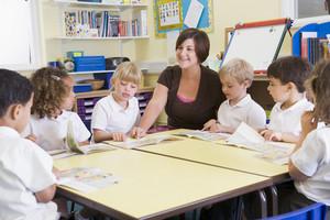Schoolchildren and their teacher reading in primary class