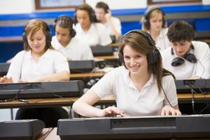 Schoolchildren practicing on a keyboard in music class