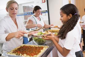 Schoolgirl holding plate of lunch in school cafeteria