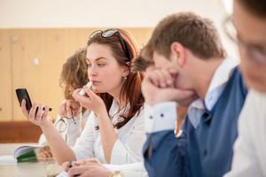 Schoolgirl putting a lipstick on her lips in a schoolroom