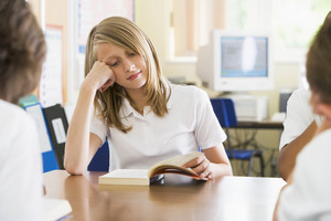 Schoolgirl reading a book in class