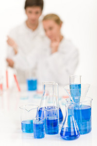 Scientists in laboratory - blue liquid in beakers