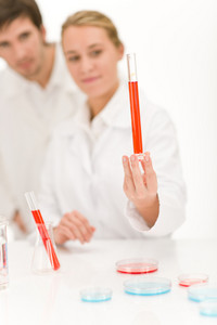 Scientists in laboratory - flu virus test tube with red liquid