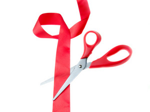 Scissors And Red Ribbon Isolated On White