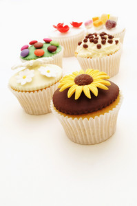 Selection Of Decorated Cup Cakes On White Background