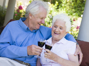 Senior couple celebrating with glass of red wine