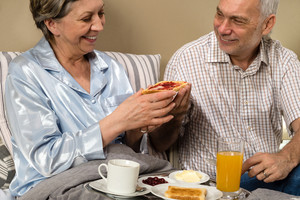 Senior couple having romantic morning breakfast in bed