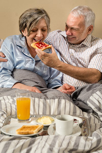 Senior couple lying in bed man feeding breakfast to woman
