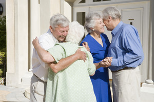 Senior couple meeting friends outside house