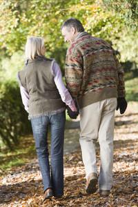 Senior couple on autumn walk through woodland
