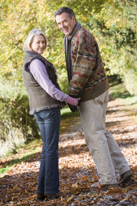 Senior couple on woodland walk through autumn woods